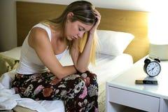 美好的年轻被用尽的妇女遭受的失眠在家坐床在卧室 免版税库存图片