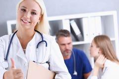 美好的微笑的女性医生陈列OK或证实标志 免版税图库摄影