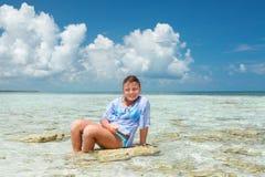 美好的微笑的快乐的小女孩开会和放松在一块石头在海洋 库存照片