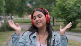 美好的快乐的女孩跳舞在听到在耳机的音乐的公园 乐趣心情 股票录像