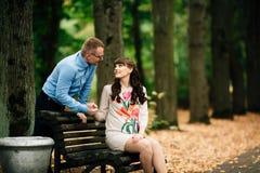 美好的怀孕的时髦的夫妇松弛外部在秋天公园坐长凳 免版税库存照片