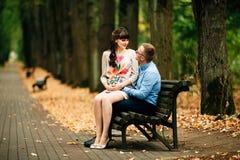 美好的怀孕的时髦的夫妇松弛外部在秋天公园坐长凳 免版税库存图片