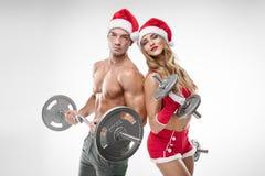美好的性感的夫妇在圣诞老人给做锻炼穿衣 免版税图库摄影