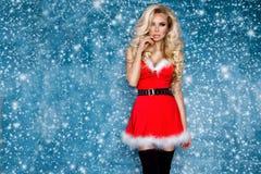 美好的性感的白肤金发的女性模型在圣诞老人帽子和礼服穿戴了 圣诞节的肉欲的女孩 免版税库存照片
