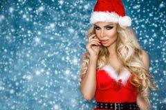 美好的性感的白肤金发的女性模型在圣诞老人帽子和礼服穿戴了 圣诞节的肉欲的女孩 库存图片