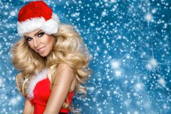 美好的性感的白肤金发的女性模型在圣诞老人帽子和礼服穿戴了 圣诞节的肉欲的女孩 免版税库存图片