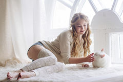 美好的性感的白肤金发的开会在与猫一起的窗口里 库存照片