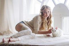 美好的性感的白肤金发的开会在与猫一起的窗口里 免版税库存图片