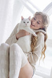 美好的性感的白肤金发的开会在与猫一起的窗口里 免版税库存照片