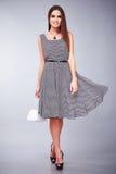 美好的性感的年轻女商人深色的头发晚上构成佩带大礼服上面高跟鞋的女衬衫裙子穿上鞋子企业克洛 库存图片