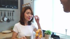 美好的愉快的亚洲夫妇互相喂养 烹调食物的男人和妇女在厨房里 股票录像