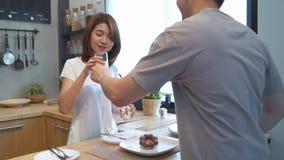 美好的愉快的亚洲夫妇互相喂养 烹调食物的男人和妇女在厨房里 股票视频
