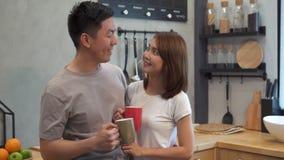 美好的愉快的亚洲夫妇在厨房里一起喝着一杯咖啡 谈话的男人和的妇女,当食用早餐时 影视素材