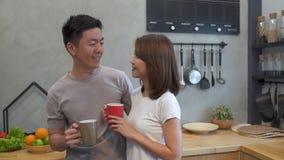 美好的愉快的亚洲夫妇在厨房里一起喝着一杯咖啡 谈话的男人和的妇女,当食用早餐时 股票视频