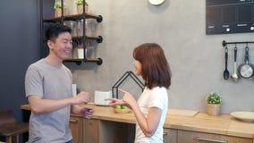 美好的愉快的亚洲夫妇在厨房里在家跳舞 年轻亚洲夫妇在家有浪漫时间听的音乐 影视素材