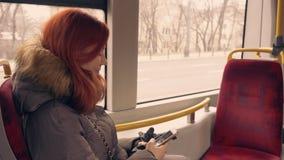 美好的愉快的在公共交通工具的女孩用途巧妙的电话 股票视频