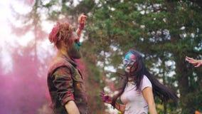 美好的愉快的夫妇亚裔女孩和白种人人跳舞的慢动作在Holi节日和投掷的五颜六色的油漆 股票录像