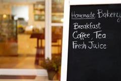 美好的手文字菜单的关闭在黑板 在咖啡馆入口前面的黑粉笔板 被弄脏的面包店和咖啡馆ba 免版税库存照片