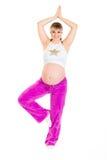 美好的执行的怀孕的微笑的女子瑜伽 免版税库存照片