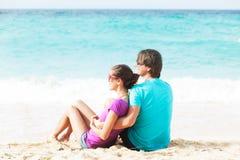 美好的新夫妇和获得乐趣坐海滩 免版税图库摄影