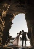 年轻美好的新娘夫妇剪影获得乐趣一起在海滩 免版税库存照片