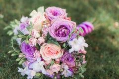 美好的新娘的婚礼五颜六色的花束有对此的金黄圆环的在草说谎 紫色,白色和桃子花 免版税库存照片