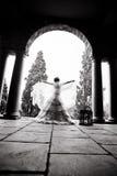 年轻美好的新娘跳舞剪影在一个有柱屋顶下 免版税库存照片