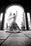 年轻美好的新娘跳舞剪影在一个有柱屋顶下 免版税图库摄影