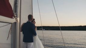 美好的新婚佳偶夫妇在船上拥抱,站立风船 新娘和新郎在婚礼装备看距离 股票录像