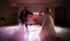 美好的新婚佳偶夫妇首先跳舞在招待会,烟surron 免版税库存图片