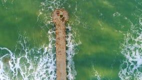 美好的日出空中寄生虫视图在海的 在海滩的残破的老桥梁 股票视频
