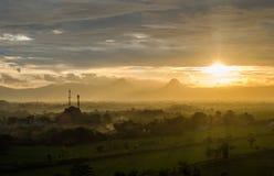 美好的日落、云彩、薄雾和山场面在金黄颜色 库存图片