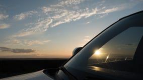 美好的日落和天空与云彩通过汽车的挡风玻璃 免版税图库摄影