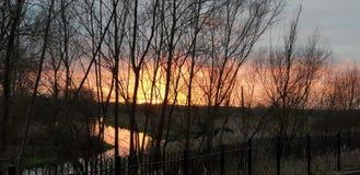 美好的日落在奥尔尼在河Ouse的米尔顿凯恩斯有橙红和桃红色天空的 图库摄影