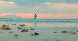 美好的日落在转动钓鱼在海洋渔夫的背景的热带 渔夫钓鱼 影视素材