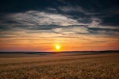 美好的日落在whetaen领域,与云彩的五颜六色的天空 免版税库存图片