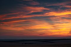 美好的日落在whetaen领域,与云彩的五颜六色的天空 库存照片