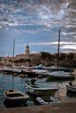 美好的日落有在岸的小镇视图,当帆船和游艇停住在海湾时 免版税库存照片