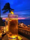 美好的日落视图和冰镇啤酒和生动的颜色在天空蔚蓝 图库摄影