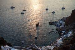 美好的日落视图的白色帆船里里外外Oia口岸有海海洋光反射背景 库存图片