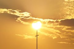 美好的日落通过与发怒天主教徒的云彩 免版税图库摄影