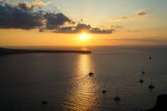 美好的日落风景海景在有帆船剪影、抽象云彩和橙色光反射的浩大的爱琴海 免版税库存图片