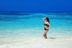 美好的时尚比基尼泳装女孩模型在热带海滩晒黑了 Ou 图库摄影