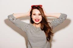 美好的明亮的深色的黑暗的方式女孩魅力她的高嘴唇查找构成镜子纵向红色反映性感的表 与红色嘴唇和红色太阳镜的魅力时髦的美好的年轻愉快的微笑的妇女模型 库存图片