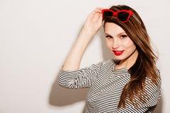 美好的明亮的深色的黑暗的方式女孩魅力她的高嘴唇查找构成镜子纵向红色反映性感的表 与红色嘴唇和红色太阳镜的魅力时髦的美好的年轻愉快的微笑的妇女模型 库存照片