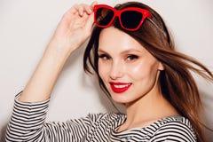 美好的明亮的深色的黑暗的方式女孩魅力她的高嘴唇查找构成镜子纵向红色反映性感的表 与红色嘴唇和红色太阳镜的魅力时髦的美好的年轻愉快的微笑的妇女模型 图库摄影