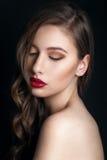 美好的明亮的深色的黑暗的方式女孩魅力她的高嘴唇查找构成镜子纵向红色反映性感的表 魅力美好的性感的时髦的深色的少妇模型特写镜头画象与明亮的构成的与红色嘴唇 免版税库存图片