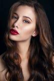 美好的明亮的深色的黑暗的方式女孩魅力她的高嘴唇查找构成镜子纵向红色反映性感的表 魅力美好的性感的时髦的深色的少妇模型特写镜头画象与明亮的构成的与红色嘴唇 免版税库存照片