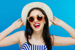 美好的明亮的深色的黑暗的方式女孩魅力她的高嘴唇查找构成镜子纵向红色反映性感的表 在夏天布料的魅力时髦的逗人喜爱的美好的少妇模型在蓝色背景的明亮的帽子 图库摄影