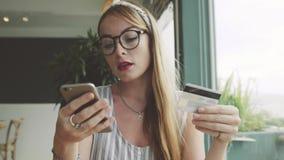美好的有信用卡和手机的妇女购买新的鞋子 免版税库存图片